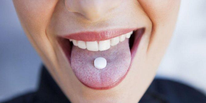 Жінка пріймає таблетку