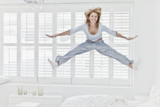 жінка стрибає на ліжку