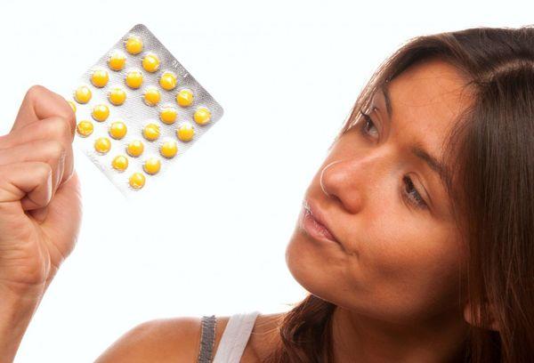 жінка з таблетками в руці